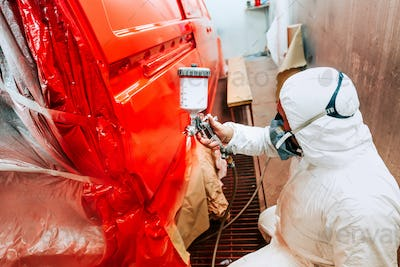 Painter working and painting a red car in paint garage