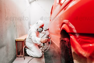 Mechanic working on painting a red car in special booth