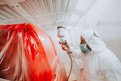 Portrait of painter working in paint booth. Mechanic painting a red car