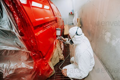 Portrait of Painter working and painting a red car in paint garage