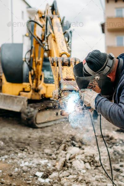 Professional welder with protection gear and mask welding broken excavator arm