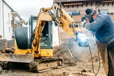Broken excavator on construction site, portrait of welder fixing