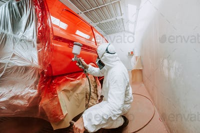 worker painting a red car in a special garage, wearing a white costume