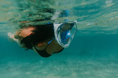 Close up view of woman snorkelling underwater wearing mask.