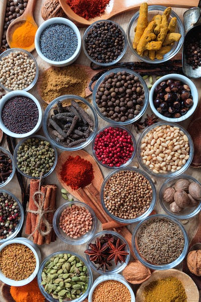 Spices and herbs flat lay, wooden background, top view.