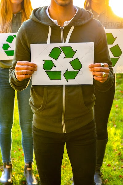 Team of volunteers holding recycling symbol placards outdoor