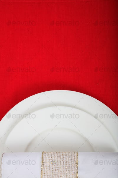 Valentine day dinner table setting. White plates on red color background