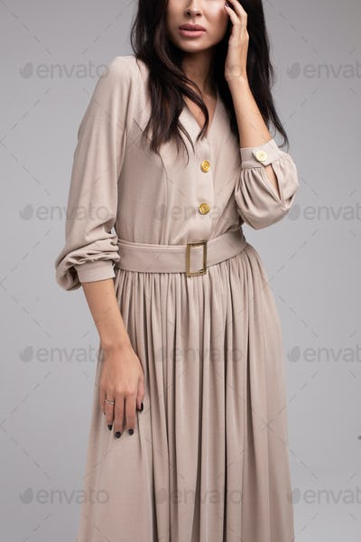 Sensual woman in casual beige dress. Studio shot