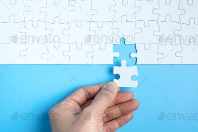 Hand complete the last piece white puzzle for business concept