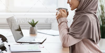 Relaxed muslim female manager drinking coffee at workplace in office