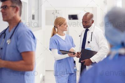 Doctor In White Coat And Nurse In Scrubs Looking At Digital Tablet In Hospital Corridor