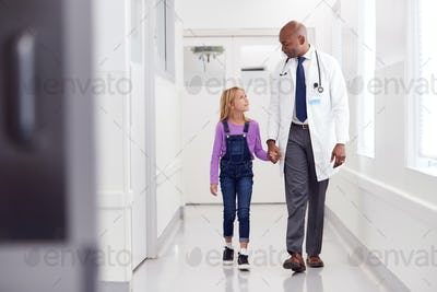 Male Paediatric Doctor Walking Along Hospital Corridor Holding Hands With Young Girl Patient