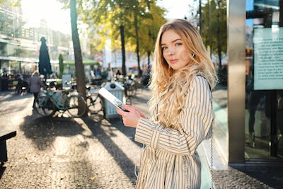 Gorgeous blond girl in stylish trench coat with tablet confidently looking in camera on sunny street