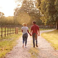 Rear View Of Romantic Couple Walking Hand In Hand Along Country Lane At Sunset