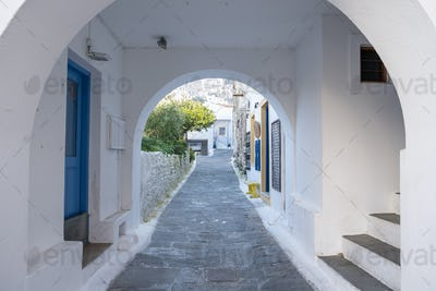 Traditional greek whitewashed buildings, cobblestone streets and stone structure arch.