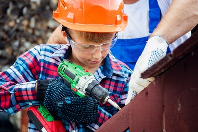 Cute boy in a construction helmet and glasses with a screwdriver in his hands building wooden dog