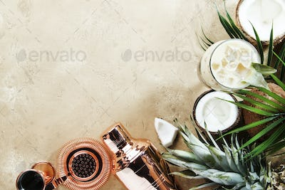 Pina Colada Cocktail on sand beige background with tropical fruits
