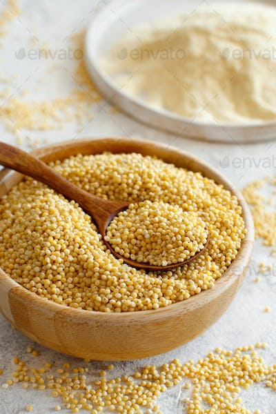 Hulled millet grain and flour in bowls