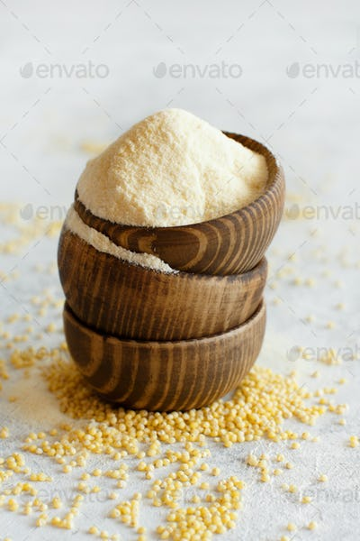Hulled millet flour in wooden bowls and grain