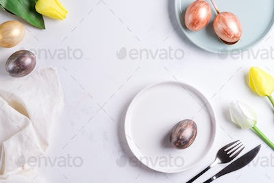 Easter table setting with spring tulips. Elegant empty plate, cutlery, napkin and golden eggs on