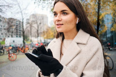 Portrait of attractive businesswoman in coat drramily using cellphone on street