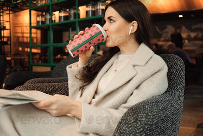 Attractive stylish businesswoman in wireless earphones drinking coffee and reading newspaper in cafe