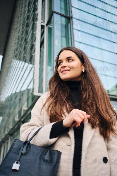 Beautiful brunette girl in coat with handbag walking around business district of city