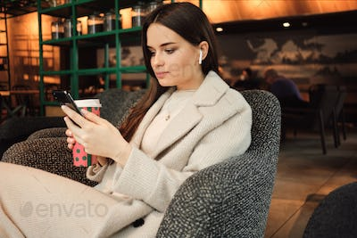 Beautiful stylish businesswoman in wireless earphones confidently using cellphone resting in cafe