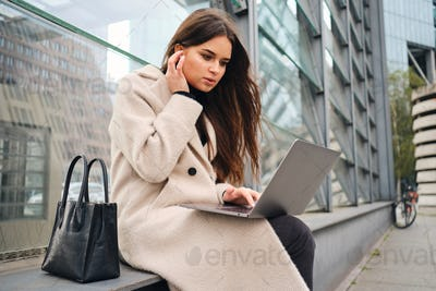 Young attractive casual businesswoman intently working on laptop on street