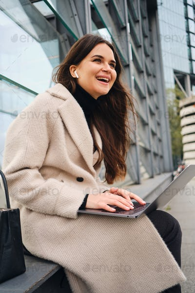 Young cheerful casual businesswoman happily working on laptop outdoor