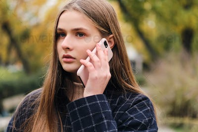 Portrait of serious girl talking on cellphone outdoor