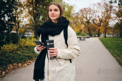 Pretty casual girl in down jacket walking around park alone with cellphone and thermo cup