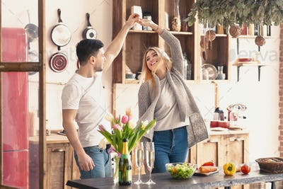 Young pair dancing at home on kitchen