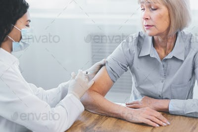 Latina doctor doing vaccination to elderly woman