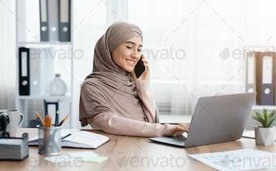Young Arabic Businesswoman Talking On Cellphone And Using Laptop In Office