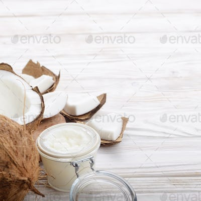 Coconut oil in airtight glass jar and shell pieces on white wooden table closeup