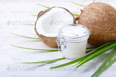 Coconut oil in airtight glass jar and shell pieces on white wooden table
