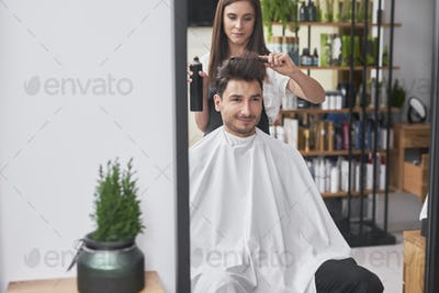 Female hairdresser  is creating trendy hairstyle her male customer