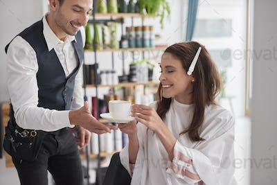 Beautiful woman drinking coffee in hair salon