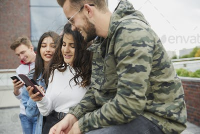 Group of young people using mobile phone on fresh air