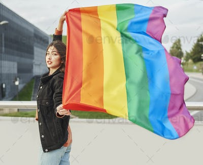 Portrait of young woman with rainbow flag