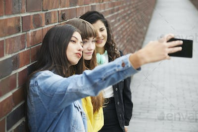 Hipster friends making a selfie by mobile phone