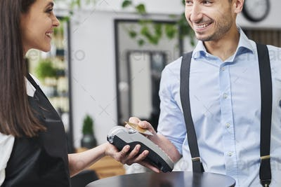 Pleased customer paying by credit card in hair salon