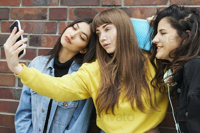 Three girls making a selfie by mobile phone