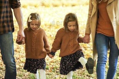Parents with children walking in autumn woods