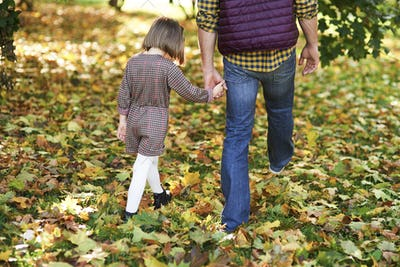 Rear view of child and father walking in autumn woods
