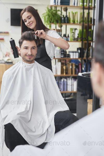 Smiling male customer sitting in hair salon
