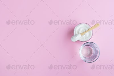 A glass water and a spoon with collagen powder on pink background.