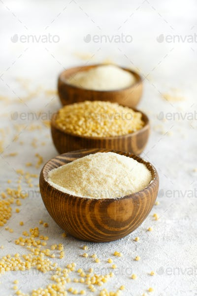 Hulled millet flour and grain in wooden bowls