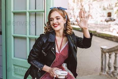 Joyful lady in leather jacket sitting near door in cafe with instant camera in hand happily